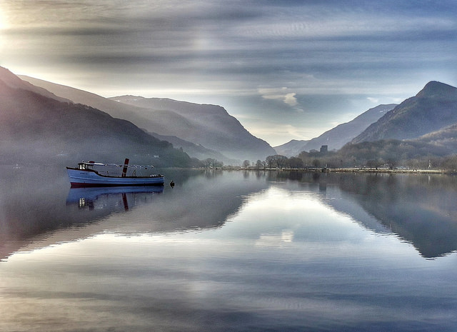 A boat floating on Llyn Padarn, with mountains beyond.